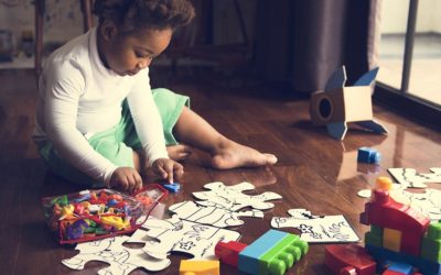 African descent kid enjoying puzzles on wooden floor