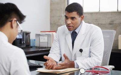 Concerned mixed race male doctor counselling male patient