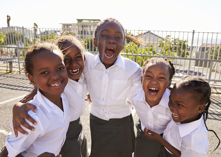 Young African schoolgirls in playground smiling to camera